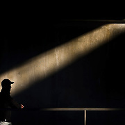A pedestrian walked past a shaft of light underneath the railroad bridge on Southwest Boulevard and W. 25th Street in the warm sunshine of temperatures in the 60's across the metro area.