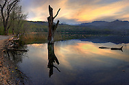 A moody view at sunset of the smaller lake (of two) of Avigliana in Piedmont, Italy. Sttiched from four vertical frames.