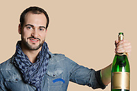 Portrait of a happy young man with champagne over colored background