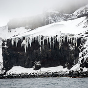 The rugged landscape of Neptunes Bellows, the entrance to Whalers Bay on Deception Island in the South Shetland Islands. Deception Island, in the South Shetland Islands, is a caldera of a volcano and is comprised of volcanic rock.