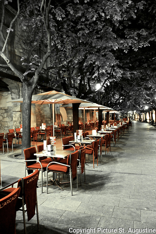 Black and white image with selective color of an outdoor restaurant in Girona, Spain. This photograph was taken at night.
