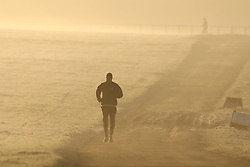 © Licensed to London News Pictures. 21/01/2020. Epsom, UK. An early morning runner braves the frosty and foggy start to the day on Epsom Downs racecourse in Surrey. Photo credit: Peter Macdiarmid/LNP