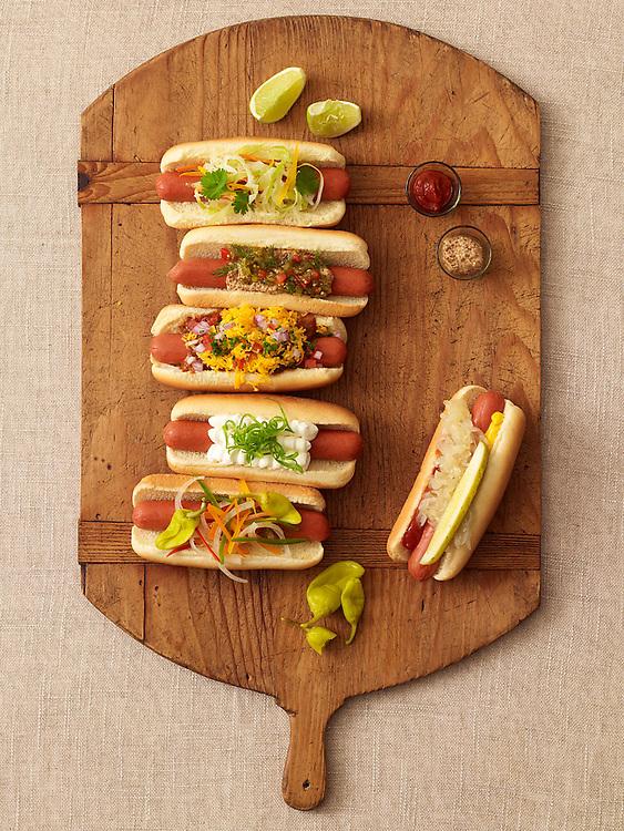 Six hotdogs on a bread board overhead