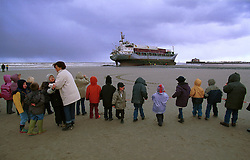 """BLANKENBERGE, BELGIUM - NOVEMBER 9, 2001 -  School children were brought to the beach by their teacher so they could see the German cargo ship """"Heinrich Behrmann"""", which was beached by heavy seas after losing power to the main engine late Thursday night at Blankenberge. The ship was heading for the port at Zeebrugge from Ireland, and was carrying dry cargo, none of which was hazardous. Unie Van Redding - En Sleepdienst N.V. was hired to free the ship. Three unsuccessful attempts were made Friday, the second attempt resulted in the injury of two workers when tug boat cables snapped. The beached ship has attracted the attention of curious tourists. (Photo © Jock Fistick)"""