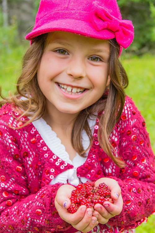 A smiling young girl shows off her collection of bright red nagoonberries in Gustavus, Alaska. MR
