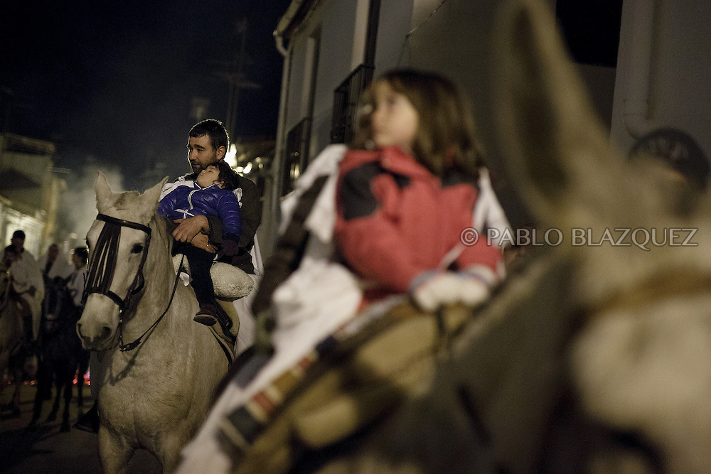 "A horseman hods an infant as he marches next to young horse riders during the ""La Encamisa"" Festival on December 7,  2014 in Torrejoncillo, Extremadura region, Spain. ""La Encamisa"" is an ancient festival in honor of Immaculate Conception. Hundreds of horsemen wearing a white sheet gather outside the church in the main square. The procession starts when a banner with the image of Immaculate Conception is delivered to the horse rider steward and people cheer and shoot blanks. There are bonfires along the way where people gather to chat, eat traditional sweets and drink local wine. The origin of this tradition is unknown but it is believed the festival comes from a military event in which people from Torrejoncillo were involved. The war in Flanders in 1585, the Battle of Pavia or a legend of the siege suffered by city of Coria. (© Pablo Blazquez)"