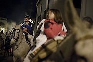 """A horseman hods an infant as he marches next to young horse riders during the """"La Encamisa"""" Festival on December 7,  2014 in Torrejoncillo, Extremadura region, Spain. """"La Encamisa"""" is an ancient festival in honor of Immaculate Conception. Hundreds of horsemen wearing a white sheet gather outside the church in the main square. The procession starts when a banner with the image of Immaculate Conception is delivered to the horse rider steward and people cheer and shoot blanks. There are bonfires along the way where people gather to chat, eat traditional sweets and drink local wine. The origin of this tradition is unknown but it is believed the festival comes from a military event in which people from Torrejoncillo were involved. The war in Flanders in 1585, the Battle of Pavia or a legend of the siege suffered by city of Coria. (© Pablo Blazquez)"""