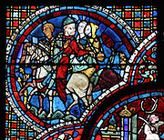 Scene showing man on horseback, possibly Lubin, turning around and looking back, from the Life of St Lubin stained glass window, 13th century, in the nave of Chartres cathedral, Eure-et-Loir, France. Lubin was a monk in the 6th century who became bishop of Chartres. Chartres cathedral was built 1194-1250 and is a fine example of Gothic architecture. Most of its windows date from 1205-40 although a few earlier 12th century examples are also intact. It was declared a UNESCO World Heritage Site in 1979. Picture by Manuel Cohen