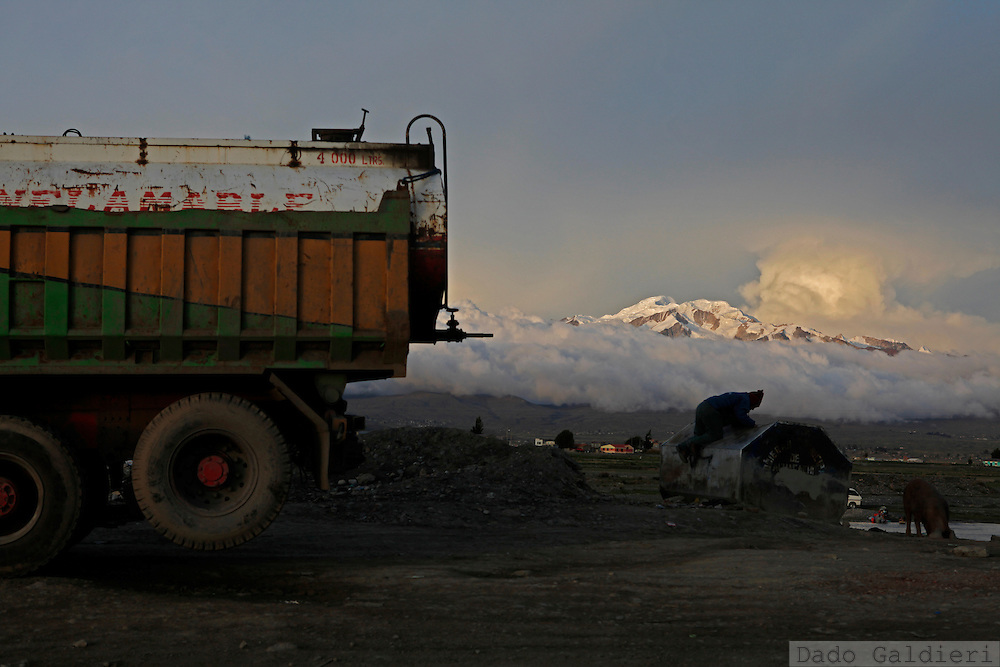 A man scavenges on a trash bin aside of a gas truck having the snow capped Illampu almost covered by storm clouds in the background in the city of Achacachi, Thursday, Dec. 10, 2009. While world leaders continuously fail to reach a global agreement to restrict carbon dioxide emissions worldwide,  underdeveloped countries like Bolivia are amongst the most probable to be stroke by climate change effects in the upcoming years.