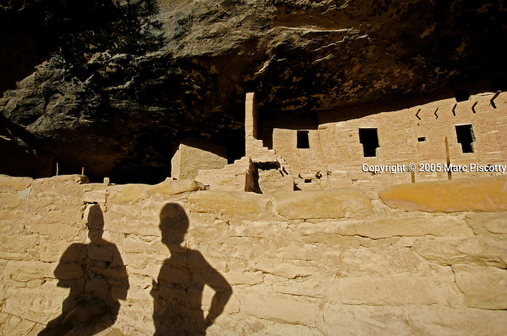 Visitors to Mesa Verde National Park cast their shadows onto a wall while touring the Spruce Tree House site at the park one afternoon. The archeological sites found in Mesa Verde National Park, near Cortez, Co., are some of the most notable and best preserved sites in the United States. Mesa Verde offers visitors a spectacular look into the lives of the Ancestral Pueblo people. The culture represented at Mesa Verde reflects more than 700 years of history. From approximately A.D. 600 through A.D. 1300 people lived and flourished in communities throughout the area, eventually building elaborate cliff dwellings in the sheltered alcoves of the canyon walls. Mesa Verde National Park is a U.S. National Park and UNESCO World Heritage Site located in Montezuma County, Colorado, United States. The park occupies 81.4 square miles (211 square kilometers) and features numerous ruins of homes and villages built by the ancient Pueblo people. It is best known for several spectacular cliff dwellings ? structures built within caves and under outcroppings in cliffs ? including Cliff Palace, which is thought to be the largest cliff dwelling in North America..(MARC PISCOTTY/ © 2005)