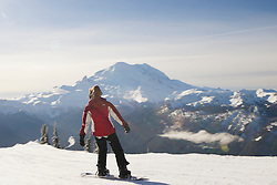 North America, United States, Washington, woman on snowboard at Crystal Mountain, with Mt. Rainier in distance