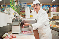 Butcher looking away while meat coming out of fly wheel slicer