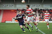 Doncaster Rovers defender Andrew Butler (6)  clears from Blackpool forward Danny Philliskirk (17)  during the Sky Bet League 1 match between Doncaster Rovers and Blackpool at the Keepmoat Stadium, Doncaster, England on 28 March 2016. Photo by Simon Davies.