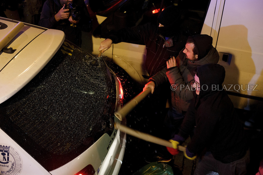 Protesters break the window of a police car after the 'Surrounding the Congress' protest at Atocha Street on December 14, 2013 in Madrid, Spain. Social movements groups called a 'Rodea el Congreso' 'Surrounding the Parliament' protest in reaction to the financial and social cuts, but also a new law the Spanish government is working that aims to set heavy fines. Around 1,500 policemen were on duty to protect the congress. The bill will set up fines of up to 30,000 euros for offenses related to social movements protests, insulting the state or offending or filming the authorities. After the demonstration some protesters clashed with riot policemen