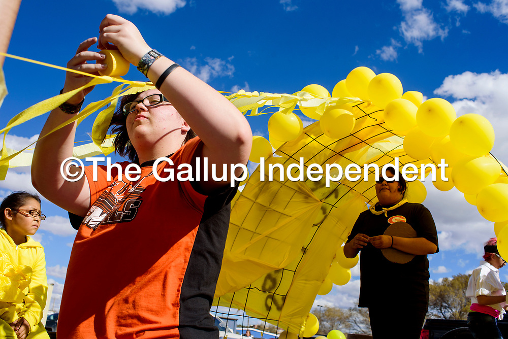 Austyn Teran helps decorate the sophomore class float for the Gallup High School Homecoming Parade in downtown Gallup Friday.