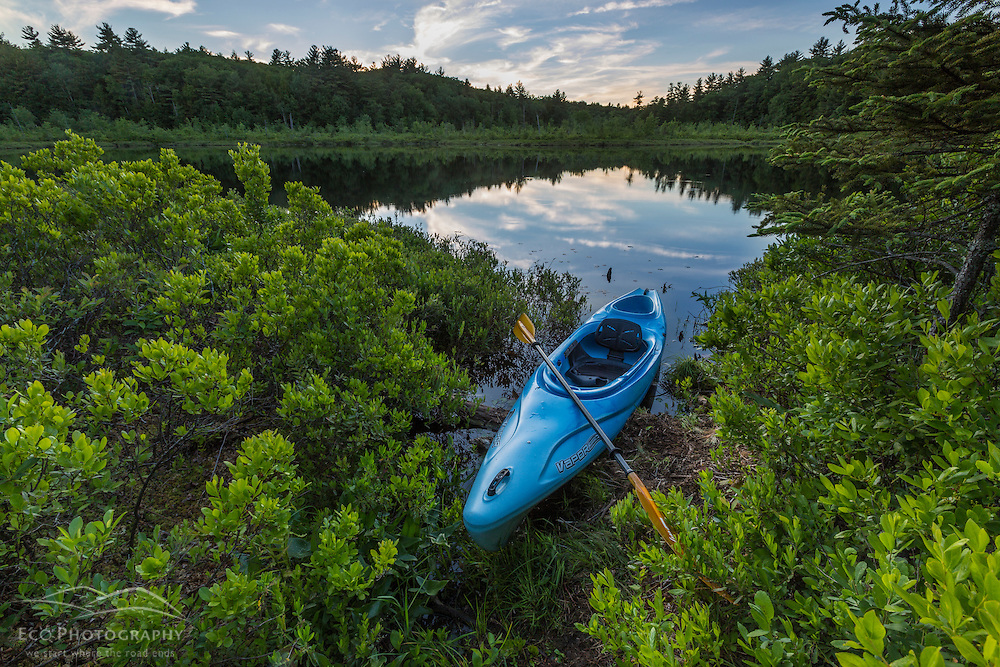 A kayak on the shore of Round Pond in Barrington, New Hampshire.
