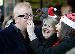 © Licensed to London News Pictures. 20/12/2011. London, United Kingdom .One of the Military Wives shoves a mince pie into Chris Evans mouth. The Military Wives Choir sing to the public outside of HMV on Oxford Street to celebrate the success of the their single..Photo credit : Chris Winter/LNP