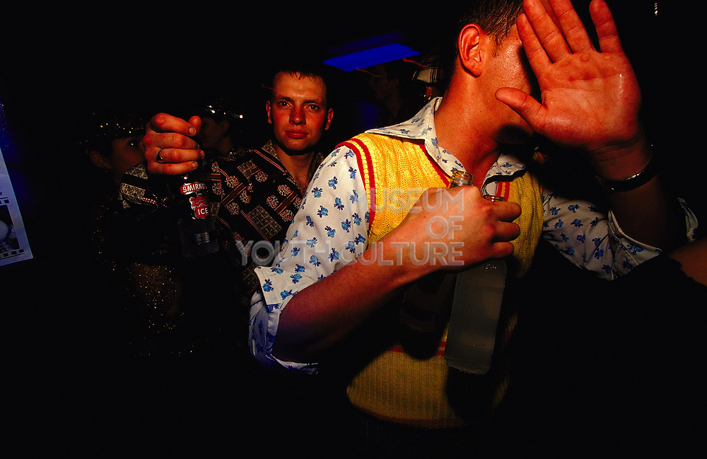 Two men in a club, one shields his face, 2000;s