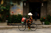 A vietnamese lady cycles to market in her colourful pyjamas, Hoi An, Vietnam