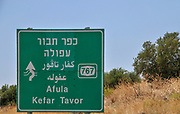 Israel, Galilee a road sign in English, Arabic and Hebrew directing to Kefar Tavor and Afula