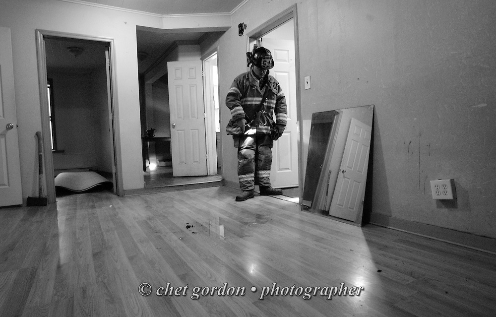 Newburgh Fire Dept. Capt. John Ryan inspects burned newspaper in the top floor of a three story building at 43 Liberty Street Newburgh, NY on Friday evening, July 1, 2011. The Newburgh Fire Department responds to nearly 3,000 calls a year.  © www.chetgordon.com/blog