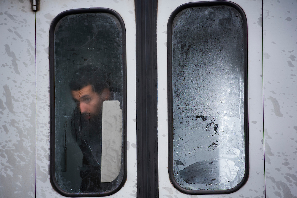 A migrant peers through a train window covered with condensation after crossing the Croatian border on September 25, 2015 in Zakany, Hungary.