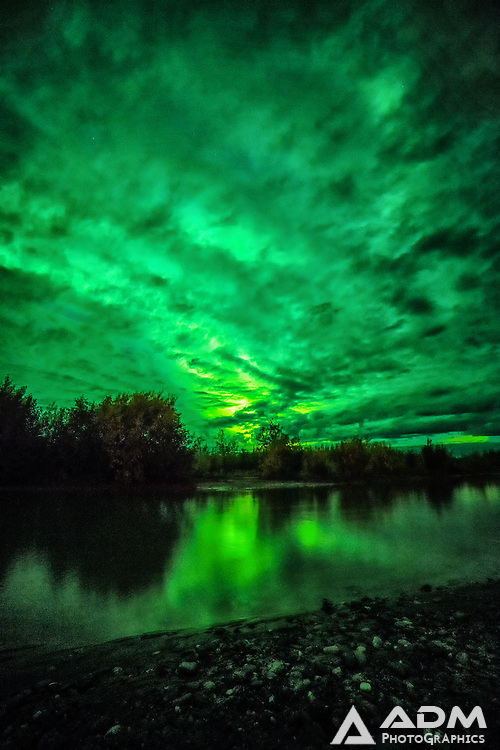 Aurora Borealis and clouds near Anderson, Alaska reflecting in the Nenana River