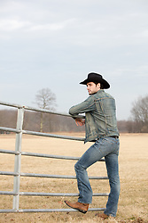 rugged cowboy leaning on a fence by an open field