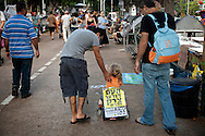 "An Israeli child in the protest encampment carries a signpost ""The people demand social justice"", calling the people to demonstrate against the rising cost of living in Israel. Tel-Aviv, Aug. 6, 2011."