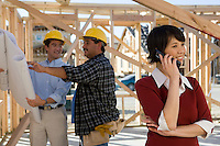Woman using mobile phone near workers on construction site