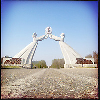 Large marble statues representing a united Korea outside of Pyongyang, North Korea. The statues preside over an empty highway outside of the capital.