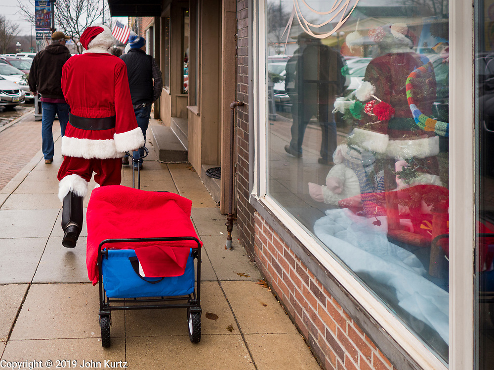 "30 NOVEMBER 2019 - WEST DES MOINES, IOWA: SANTA CLAUS walks down 5th Street, the main business street in West Des Moines, Saturday. He was handing out gifts to children on Small Business Saturday. ""Small Business Saturday"" was first observed in the United States on November 27, 2010, as a counterpart to Black Friday and Cyber Monday, which are generally considered events at malls, ""big box"" stores and e-commerce retailers. Small Business Saturday encourages holiday shoppers to patronize brick and mortar businesses that are small and local. Small Business Saturday is a registered trademark of American Express.      PHOTO BY JACK KURTZ"