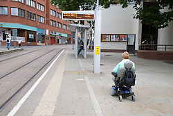 Woman wheelchair user going towards a tram stop,