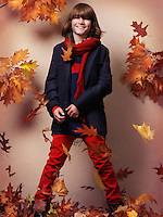 Smiling boy wearing fall clothes, blue jacket with red pants and scarf, standing on fallen red leaves, autumn children fashion artistic photo