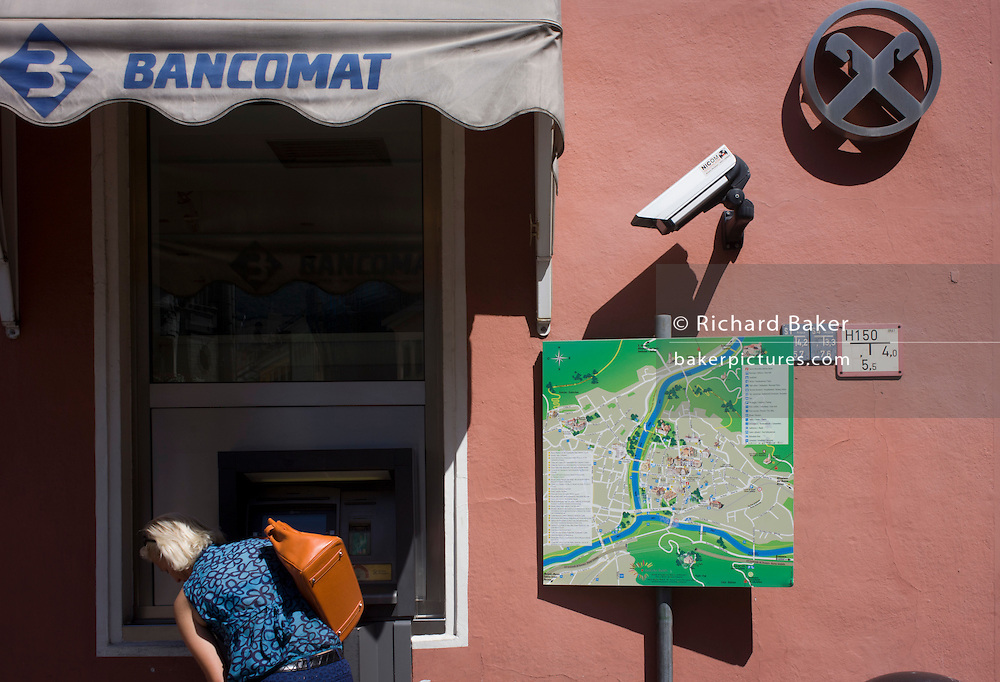 Under the gaze of CCTV, a customer uses a Bancomat cash dispenser in the northern Italian south Tyrolean city of Bozen-Bolzano.