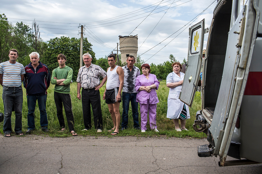 VOLNOVAKHA, UKRAINE - MAY 22:  Onlookers and hospital staff watch as the bodies of Ukrainian soldiers killed during an attack on a military checkpoint earlier in the day by unknown forces are carried into the morgue on May 22, 2014 in Volnovakha, Ukraine. Authorities reported fifteen soldiers were killed and 31 injured. (Photo by Brendan Hoffman/Getty Images) *** Local Caption ***