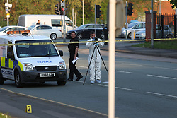 12.05.2016 Manchester UK: Police and Forensic officers at the scene in Moss Lane East , Moss Side where a male was hit by and car and other males got out of another car and stabbed the victim in broad day light. Fireman from a hear by fire station went to the aid of the victim. a spokesman said Greater Manchester Fire and Rescue Service confirmed staff from the station performed CPR and gave the victim 'oxygen therapy' before handing him over to paramedics when they arrived