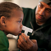 Aaron Fulbright gives a breathing treatment to son Aaron Jr., 7, after the boy had an asthma attack. Fulbright is looking for steady work, but the single father says his three sons' health and behavior problems make it more difficult.