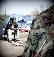 "Robert Burgins sits by his campfire out side his tent that is his home at a homeless encampment or ""tent city"" on the banks of the American River in Sacramento, CA."
