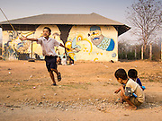 06 MARCH 2014 - MAE SOT, TAK, THAILAND: Children play at the side of the school before classes start at the Sky Blue School. There are approximately 140 students in the Sky Blue School, north of Mae Sot. The school is next to the main landfill for Mae Sot and serves the children of the people who work in the landfill. The school relies on grants and donations from Non Governmental Organizations (NGOs). Reforms in Myanmar have alllowed NGOs to operate in Myanmar, as a result many NGOs are shifting resources to operations in Myanmar, leaving Burmese migrants and refugees in Thailand vulnerable. The Sky Blue School was not able to pay its teachers for three months during the current school year because money promised by a NGO wasn't delivered when the NGO started to support schools in Burma. The school got an emergency grant from the Burma Migrant Teachers' Association and has since been able to pay the teachers.      PHOTO BY JACK KURTZ