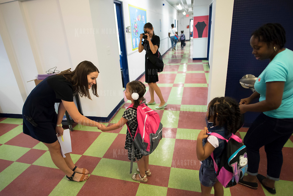 August 24, 2015 - New York, NY : Elena Donin, top center, snaps a photo of her daughter Veronica, foreground center, as she is greeted by Special Education Coordinator Jennifer Lotito, left, as they arrive for the first day of school at the International Charter School of New York (ICS) on Monday morning, August 24. Founded by Matthew Levey, a former diplomat and father of three, ICS, opened its doors for the first day of classes -- and the first time ever -- to kindergarteners and their parents on Monday, August 24. CREDIT: Karsten Moran for The New York Times