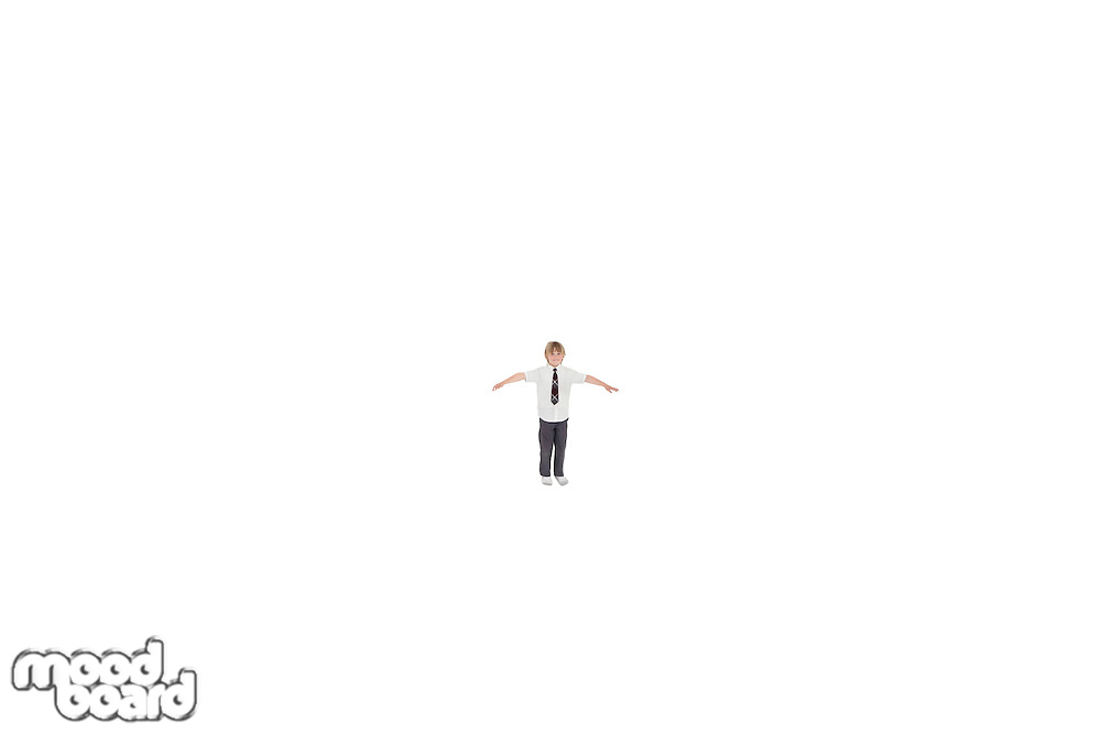 Elementary boy standing at distance with arms outstretched over white background