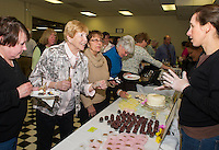 Marge Linn and Peg Murphy try a sampling of sweet treats from Sarah Goren and Tanaya Call of Twin Muffin Baking Company Sunday afternoon during the annual Altrusa Taste of the Lakes Region at the Opechee Conference Center.  (Karen Bobotas/for the Laconia Daily Sun)