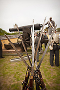 Civil war rifles stacked as Confederate re-enactors man a giant Civil War canon in Fort Moultrie aimed at Fort Sumter in Charleston Harbor Charleston, SC. The re-enactors are part of the 150th commemoration of the US Civil War.