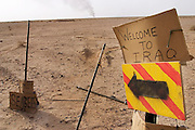 A hand painted sign just across the Kuwait border in Iraq. The Rumaila field is one of Iraq's biggest oil fields with five billion barrels in reserve. Many of the wells are 10,000 feet deep and produce huge volumes of oil and gas under tremendous pressure, which makes capping them very difficult and dangerous. Smoke from one of the burning oil wells can be seen in the distance. Rumaila is also spelled Rumeilah.