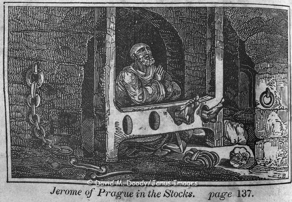 "Jerome of Prague in the stocks. Protestant vs Catholic violence. Vintage Woodcut Illustration from: ""Book of Martyrs"" Tortures carried out in the name of religion."