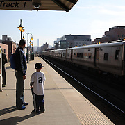 At games end a young fan waits on the train platform for the train home after the New York Yankees Vs Toronto Blue Jays season opening day at Yankee Stadium, The Bronx, New York. 6th April 2015. Photo Tim Clayton