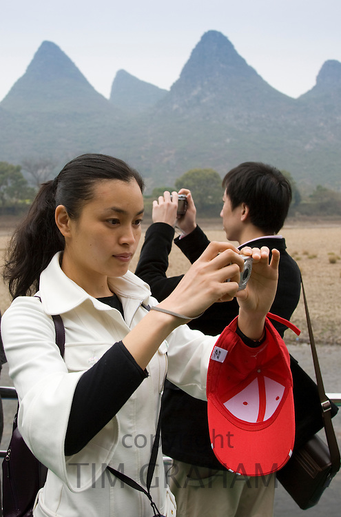 Tourists take photographs as they travel by boat along Li River between Guilin and Yangshuo, China