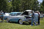 Westbury, New York, USA. June 12, 2016. Visitors are examining engine under the open hood of turquois and white 1955 Buick Special, owned by Rick D'Alessandro of Masapequa, at the Antique and Collectible Auto Show at the 50th Annual Spring Meet at Old Westbury Gardens, in the Gold Coast of Long Island, and sponsored by Greater New York Region, GNYR, Antique Automobile Club of America, AACA. Participating vehicles in the judged show included hundreds of domestic and foreign, antique, classic, collectible, and modern cars and trucks.
