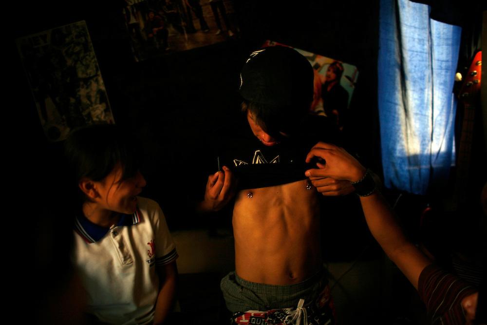 Juan Miguel, 16, shows of his piercing, in the Diaz Ordaz colonia in Ciudad Juarez, Chihuahua Mexico on April 28, 2010.